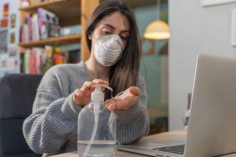 Frau mit Gesichtsmaske deinfiziert sich die Hände im Büro