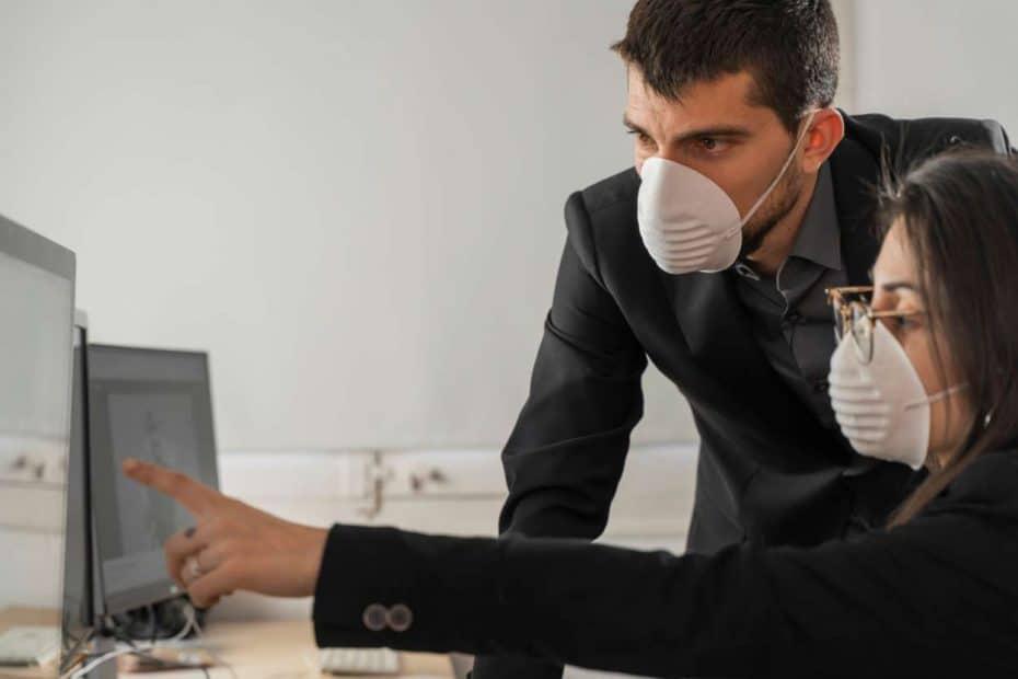 Angestellte mit Gesichtsmaske arbeiten am PC