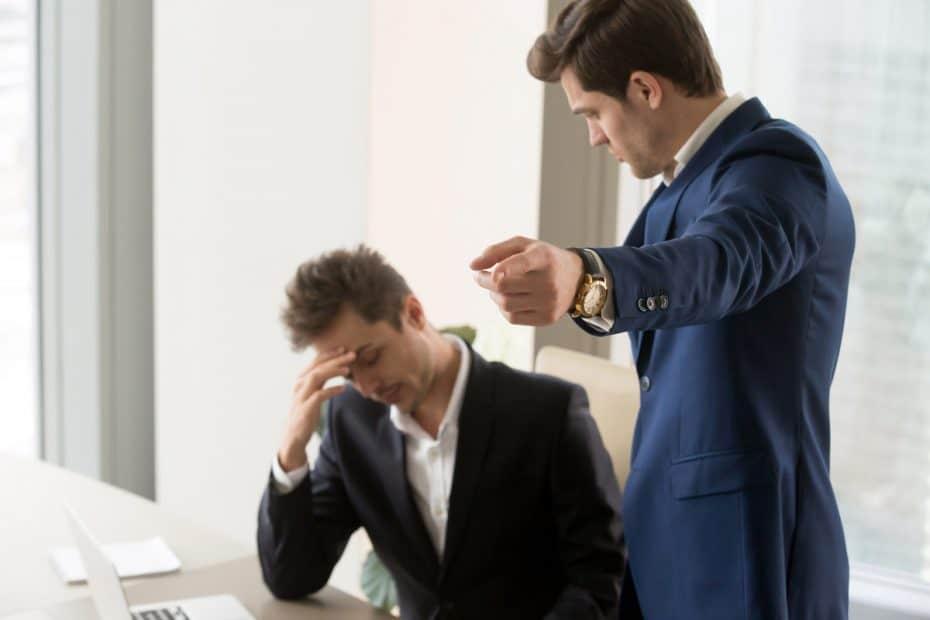 wütender Chef zeigt Arbeitnehmer nach fristloser Kündigung auf den Ausgang
