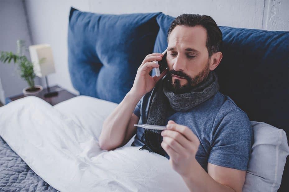 Kranker Mann im Bett mit Fieberthermometer und Telefon