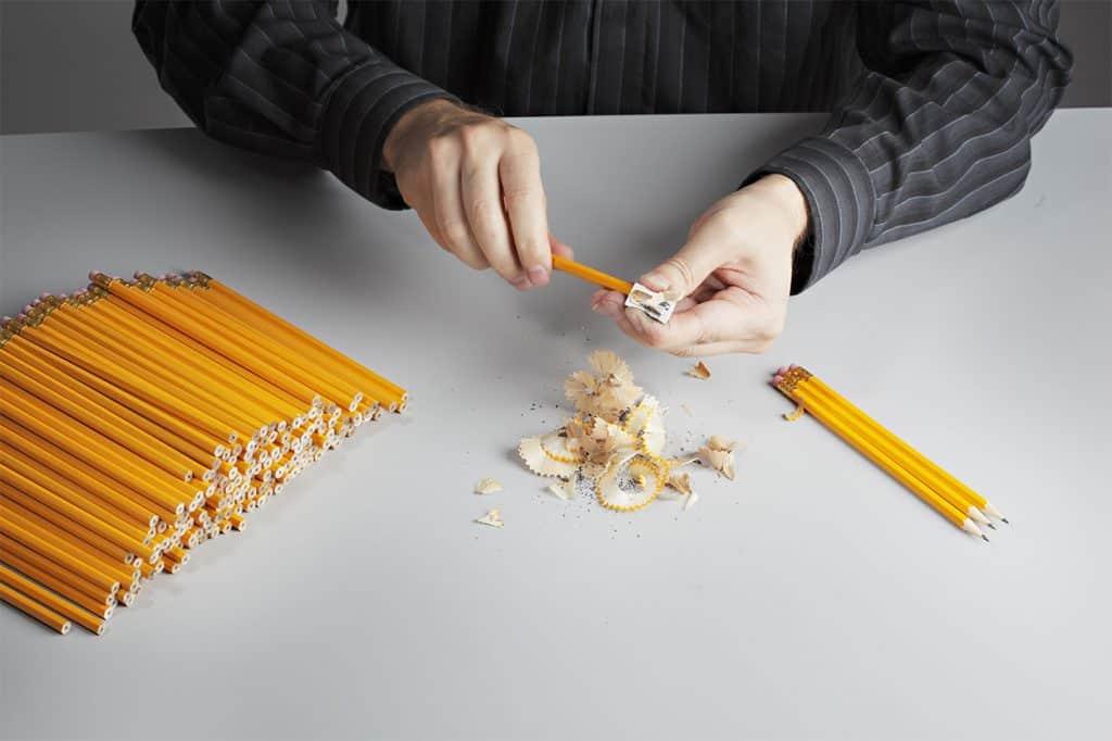 Mann spitzt Bleistifte an