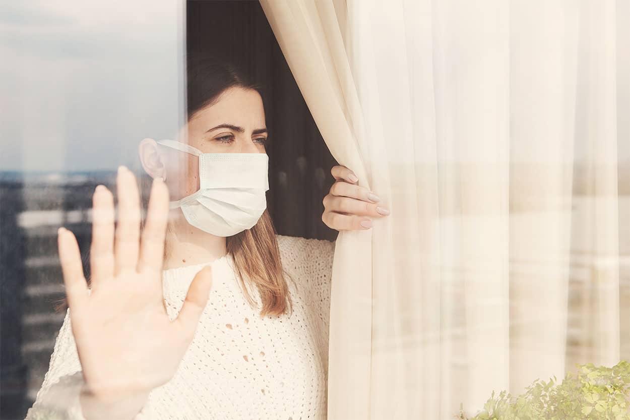 Frau mit Atemschutzmaske hinter Fenster