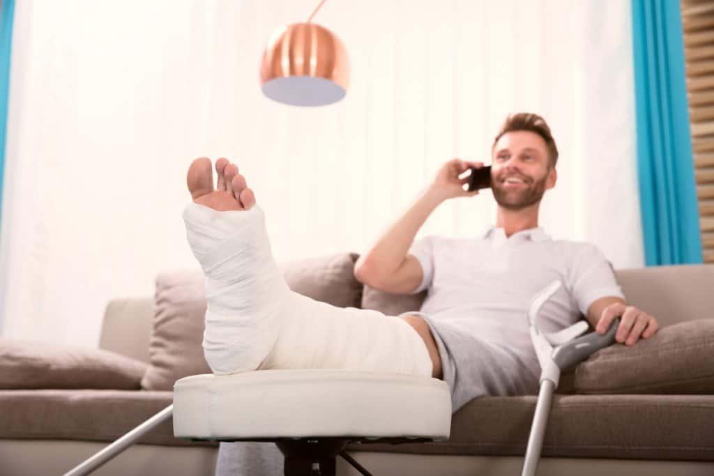 Glücklicher Mann mit Krücke und Gips Bein mit Telefon in der Hand