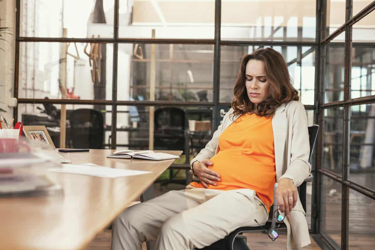 Schwangere Mitarbeiterin sitzt im Büro bei der Arbeit