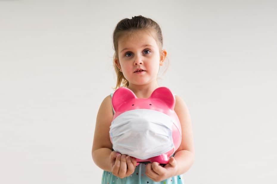 Mädchen mit Sparschwein, das eine Maske trägt