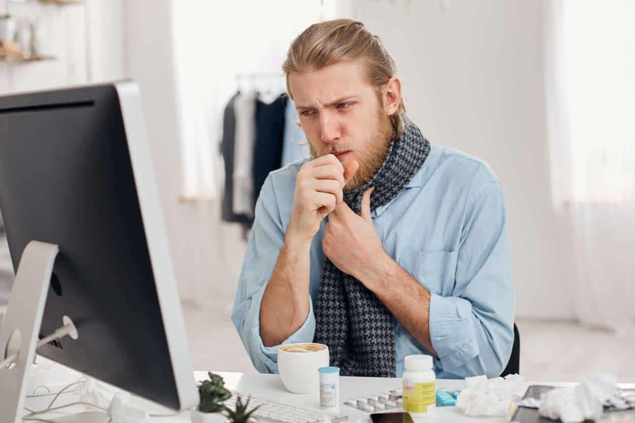 Mann arbeitet krank am Computer