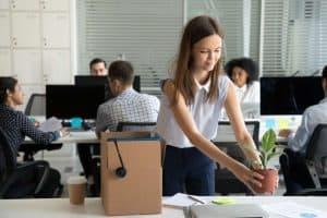 Frau stellt Blumentopf an ihren neuen Arbeitsplatz