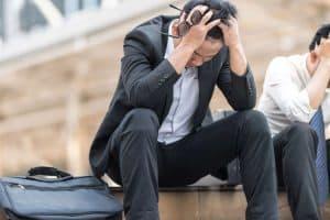 Mann sitzt nach Jobverlust traurig auf einer Treppe