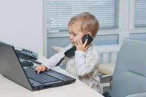 Mitbringen eines Kindes ins Büro: Das mitgebrachte Kleinkind sitzt auf dem Schreibtischstuhl im Büro, hält den Telefonhörer und tippt auf dem Laptop.