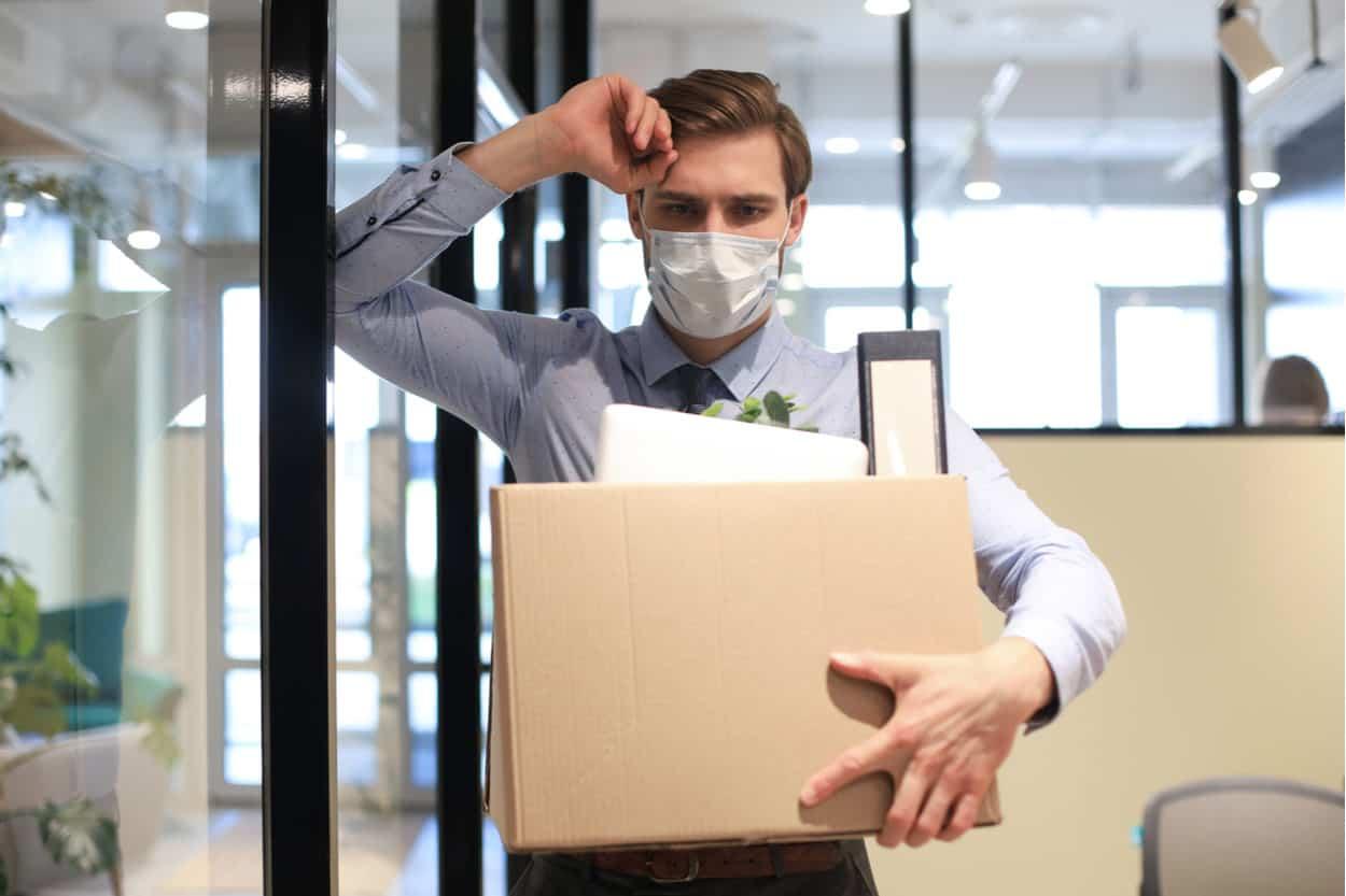 Arbeitnehmer gekündigt mit Karton und Mundschutz