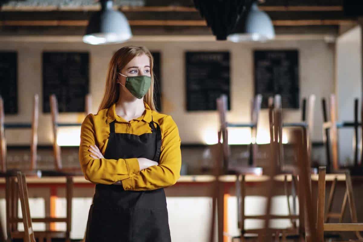Kellnerin mit Corona-Maske steht in geschlossenem Restaurant