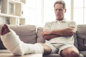 Mann mit gebrochenem Bein auf Couch