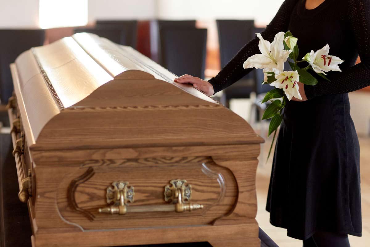 ein schwarz gekleidete junge Frau, Erbin, hält ihre Hand auf dem Sarg ihres Ehemannes.