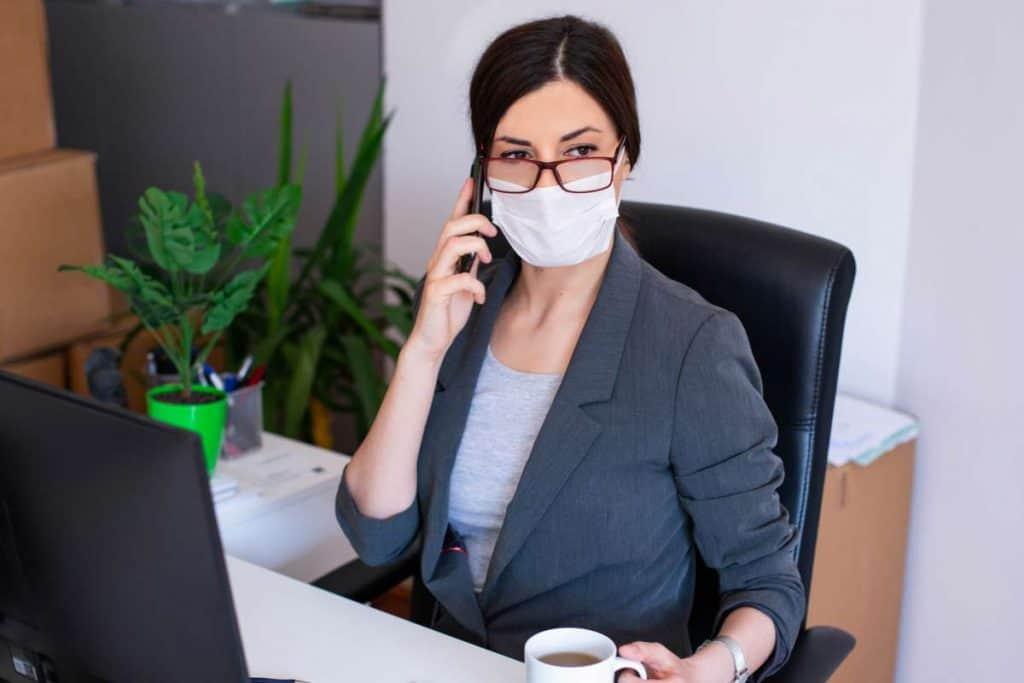 Frau mit Maske im Büro