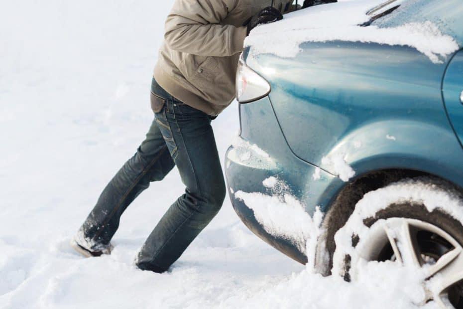 Mann schiebt Auto Pkw im Schnee